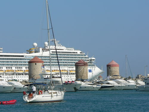 ancient wind mills with cruise liner in background